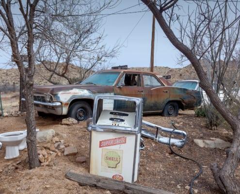 Zapfsäule und verrosterter Wagen aus den 50er